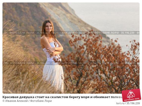 Красивая девушка стоит на скалистом берегу моря и обнимает полевые цветы. Стоковое фото, фотограф Иванов Алексей / Фотобанк Лори