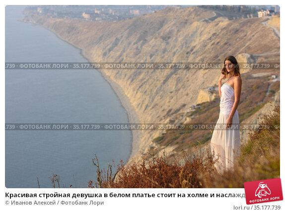 Красивая стройная девушка в белом платье стоит на холме и наслаждается прекрасным видом на закате солнца. Стоковое фото, фотограф Иванов Алексей / Фотобанк Лори