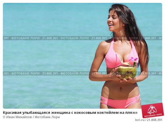 Красивая улыбающаяся женщина с кокосовым коктейлем на пляже. Стоковое фото, фотограф Иван Михайлов / Фотобанк Лори