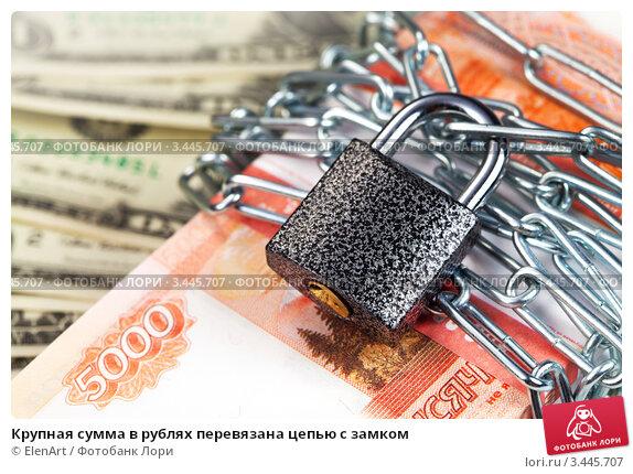 Крупная сумма в рублях перевязана цепью с замком. Стоковое фото, фотограф ElenArt / Фотобанк Лори