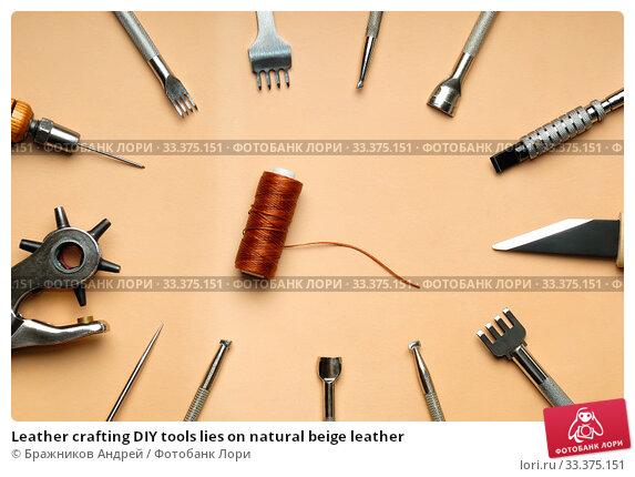 Leather crafting DIY tools lies on natural beige leather. Стоковое фото, фотограф Бражников Андрей / Фотобанк Лори