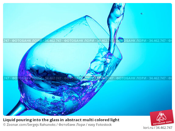 Liquid pouring into the glass in abstract multi colored light. Стоковое фото, фотограф Zoonar.com/Sergejs Rahunoks / easy Fotostock / Фотобанк Лори