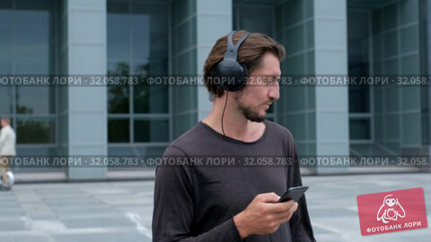 Listening music Freelancer Man in the big urban city working with a laptop phone camera and headphones. Стоковое видео, видеограф Aleksejs Bergmanis / Фотобанк Лори