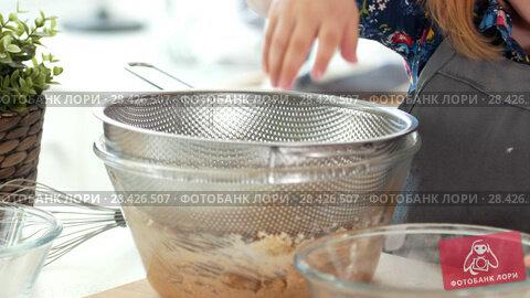 Купить «Little girl baker sifts flour through a sieve», видеоролик № 28426507, снято 22 мая 2018 г. (c) Константин Шишкин / Фотобанк Лори