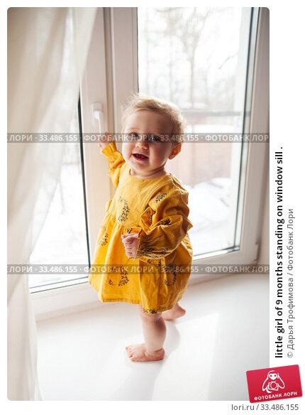 little girl of 9 months standing on window sill . Стоковое фото, фотограф Дарья Филимонова / Фотобанк Лори