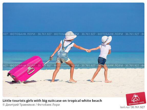 Купить «Little tourists girls with big suitcase on tropical white beach», фото № 30761927, снято 5 апреля 2015 г. (c) Дмитрий Травников / Фотобанк Лори