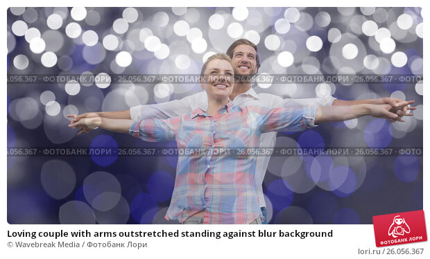 Купить «Loving couple with arms outstretched standing against blur background», фото № 26056367, снято 23 марта 2019 г. (c) Wavebreak Media / Фотобанк Лори