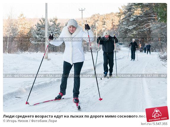 Люди среднего возраста едут на лыжах по дороге мимо соснового леса, эксклюзивное фото № 5547355, снято 25 января 2014 г. (c) Игорь Низов / Фотобанк Лори