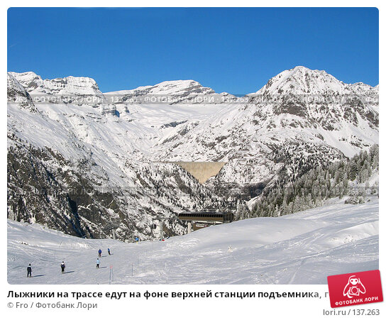 Лыжники на трассе едут на фоне верхней станции подъемника, горы и дамбы, фото № 137263, снято 26 марта 2017 г. (c) Fro / Фотобанк Лори