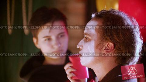Купить «Make-up artist applying paint on the man clown in the dressing room», видеоролик № 32391839, снято 20 ноября 2019 г. (c) Константин Шишкин / Фотобанк Лори