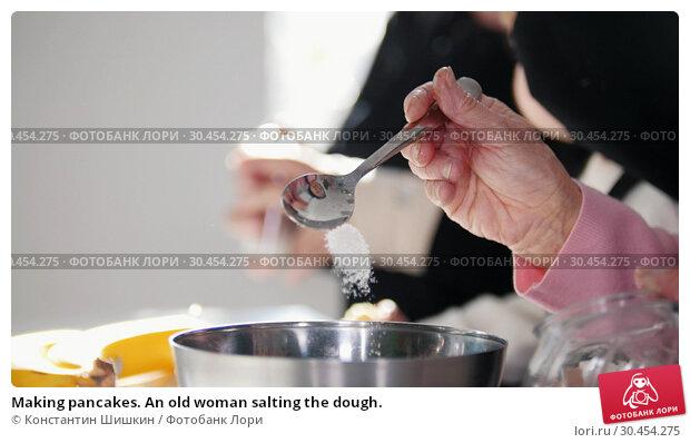 Making pancakes. An old woman salting the dough. Стоковое фото, фотограф Константин Шишкин / Фотобанк Лори