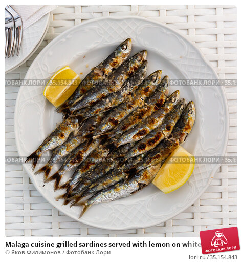 Malaga cuisine grilled sardines served with lemon on white plate on wooden table. Стоковое фото, фотограф Яков Филимонов / Фотобанк Лори