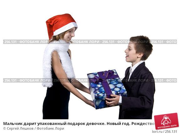 Мальчик дарит упакованный подарок девочке. Новый год. Рождество., фото № 256131, снято 25 ноября 2007 г. (c) Сергей Лешков / Фотобанк Лори