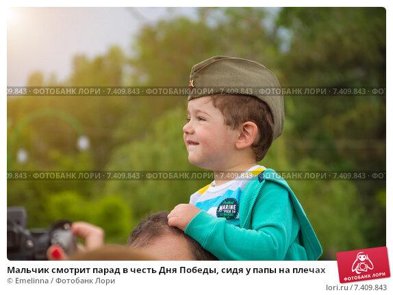 Мальчик смотрит парад в честь Дня Победы, сидя у папы на плечах (2015 год). Редакционное фото, фотограф Emelinna / Фотобанк Лори