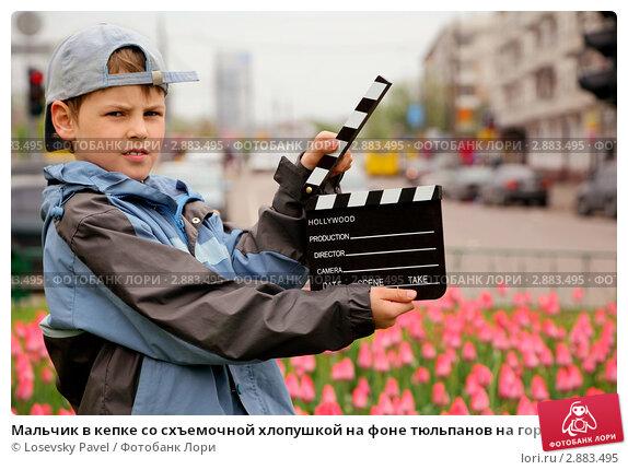 Мальчик в кепке со схъемочной хлопушкой на фоне тюльпанов на городской улице. Стоковое фото, фотограф Losevsky Pavel / Фотобанк Лори