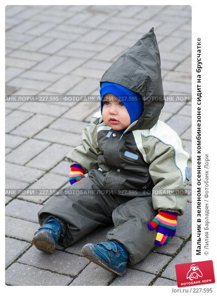Мальчик в зеленом осеннем комбинезоне сидит на брусчатке, фото № 227595, снято 12 октября 2007 г. (c) Лилия Барладян / Фотобанк Лори