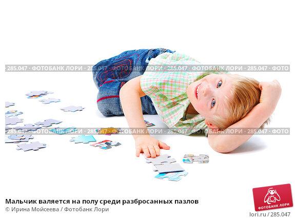 Мальчик валяется на полу среди разбросанных пазлов, фото № 285047, снято 29 марта 2008 г. (c) Ирина Мойсеева / Фотобанк Лори