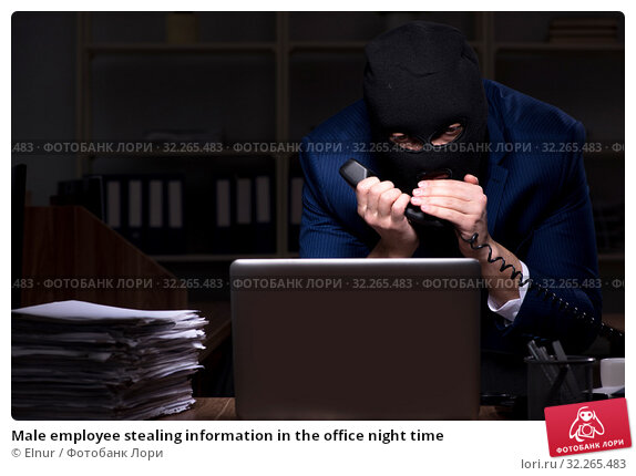 Male employee stealing information in the office night time. Стоковое фото, фотограф Elnur / Фотобанк Лори