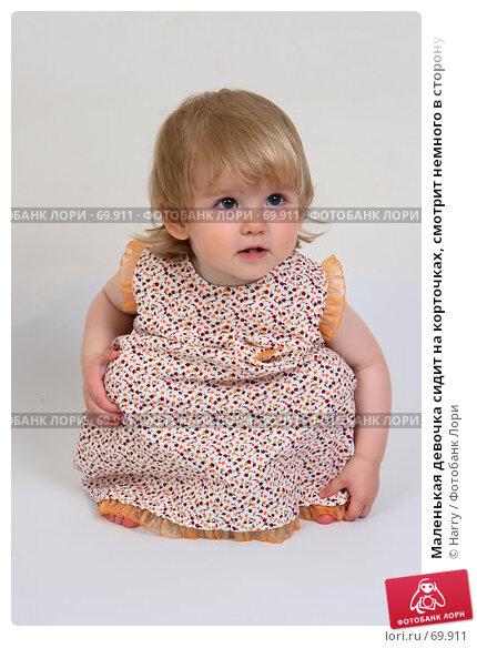 Маленькая девочка сидит на корточках, смотрит немного в сторону, фото № 69911, снято 2 июля 2007 г. (c) Harry / Фотобанк Лори