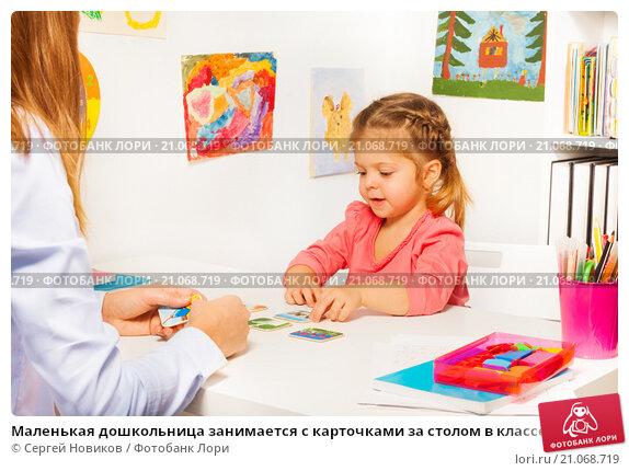Купить «Маленькая дошкольница занимается с карточками за столом в классе», фото № 21068719, снято 13 декабря 2015 г. (c) Сергей Новиков / Фотобанк Лори