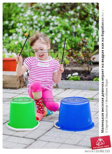 Купить «Маленькая веселая девочка играет на ведрах как на барабанах на улице», фото № 23082723, снято 27 мая 2016 г. (c) Сергей Завьялов / Фотобанк Лори