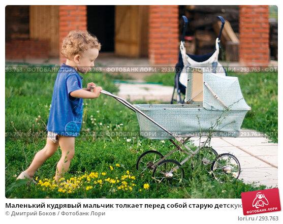 Маленький кудрявый мальчик толкает перед собой старую детскую коляску, фото № 293763, снято 15 июля 2006 г. (c) Дмитрий Боков / Фотобанк Лори
