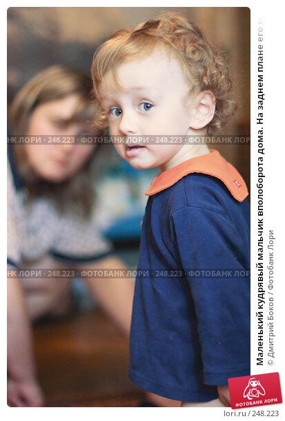Маленький кудрявый мальчик вполоборота дома. На заднем плане его мать, фото № 248223, снято 13 мая 2006 г. (c) Дмитрий Боков / Фотобанк Лори