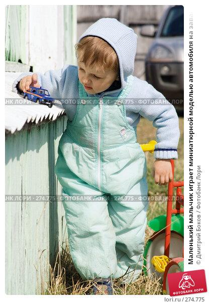 Маленький мальчик играет миниатюрной моделью автомобиля на завалинке деревенского дома, фото № 274775, снято 20 апреля 2008 г. (c) Дмитрий Боков / Фотобанк Лори
