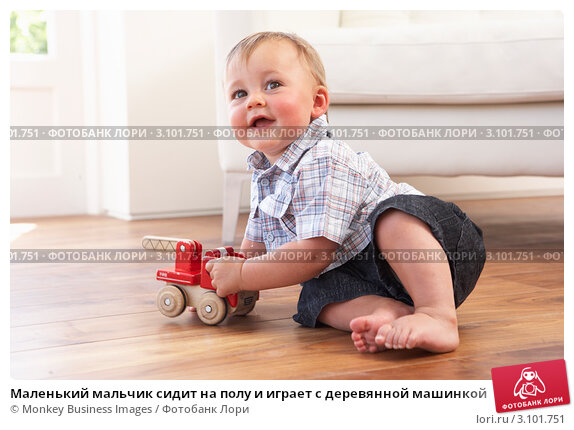 Маленький мальчик сидит на полу и играет с деревянной машинкой, фото № 3101751, снято 19 июля 2010 г. (c) Monkey Business Images / Фотобанк Лори