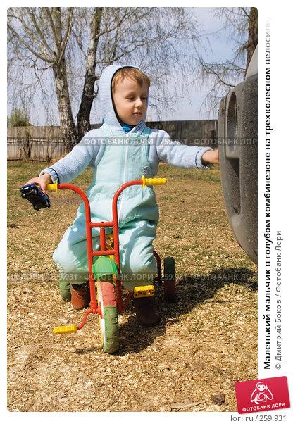 Маленький мальчик в голубом комбинезоне на трехколесном велосипеде у бампера внедорожника в деревне на фоне деревянного забора, фото № 259931, снято 20 апреля 2008 г. (c) Дмитрий Боков / Фотобанк Лори