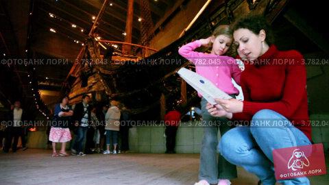 Купить «Мама с дочкой читают буклет в Музее Васа в Стокгольме», видеоролик № 3782043, снято 12 июля 2012 г. (c) Losevsky Pavel / Фотобанк Лори