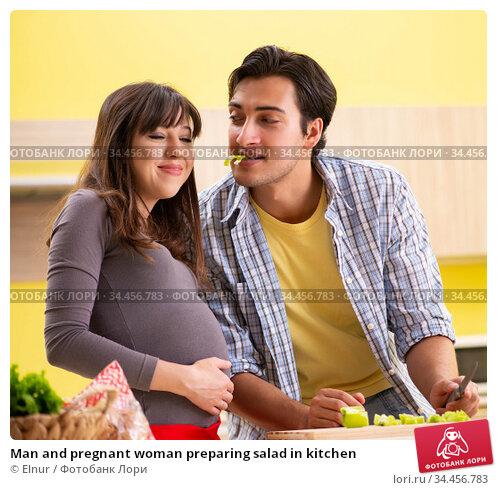 Man and pregnant woman preparing salad in kitchen. Стоковое фото, фотограф Elnur / Фотобанк Лори