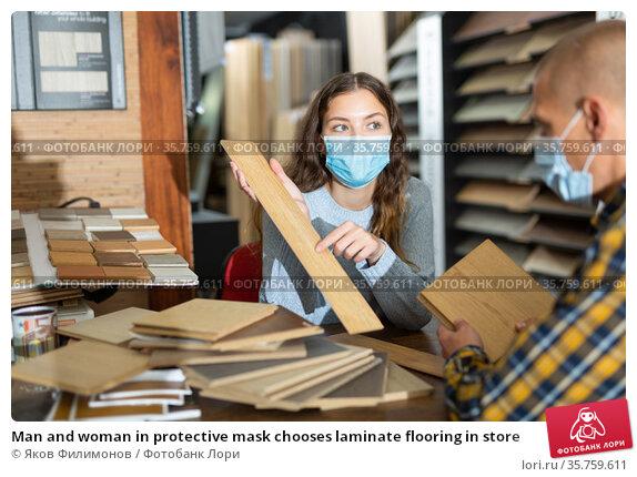 Man and woman in protective mask chooses laminate flooring in store. Стоковое фото, фотограф Яков Филимонов / Фотобанк Лори