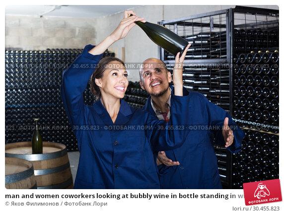 man and women coworkers looking at bubbly wine in bottle standing in wine cellar. Стоковое фото, фотограф Яков Филимонов / Фотобанк Лори