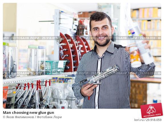Купить «Man choosing new glue gun», фото № 29918059, снято 5 апреля 2017 г. (c) Яков Филимонов / Фотобанк Лори