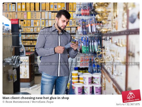 Купить «Man client choosing new hot glue in shop», фото № 32367875, снято 5 апреля 2017 г. (c) Яков Филимонов / Фотобанк Лори