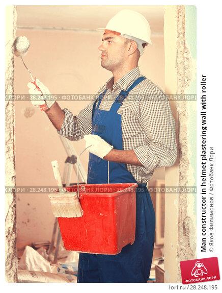 Купить «Man constructor in helmet plastering wall with roller», фото № 28248195, снято 18 мая 2017 г. (c) Яков Филимонов / Фотобанк Лори