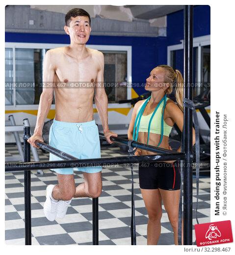 Купить «Man doing push-ups with trainer», фото № 32298467, снято 16 июля 2018 г. (c) Яков Филимонов / Фотобанк Лори