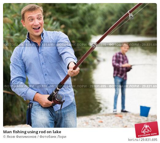Купить «Man fishing using rod on lake», фото № 29831695, снято 23 марта 2019 г. (c) Яков Филимонов / Фотобанк Лори