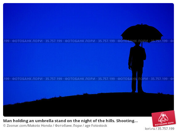 Man holding an umbrella stand on the night of the hills. Shooting... Стоковое фото, фотограф Zoonar.com/Makoto Honda / age Fotostock / Фотобанк Лори