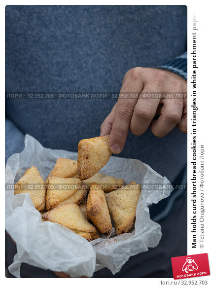 Man holds curd shortbread cookies in triangles in white parchment paper. Стоковое фото, фотограф Tetiana Chugunova / Фотобанк Лори