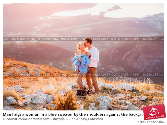 Man hugs a woman in a blue sweater by the shoulders against the background... Стоковое фото, фотограф Zoonar.com/Nadtochiy.com / easy Fotostock / Фотобанк Лори