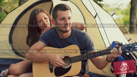 Купить «Man playing guitar for his girlfriend sitting at the camping tent», видеоролик № 29030071, снято 30 августа 2018 г. (c) Илья Шаматура / Фотобанк Лори