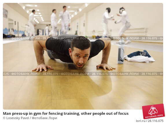 Купить «Man press-up in gym for fencing training, other people out of focus», фото № 28116075, снято 9 февраля 2017 г. (c) Losevsky Pavel / Фотобанк Лори