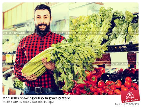Купить «Man seller showing celery in grocery store», фото № 26969539, снято 15 ноября 2016 г. (c) Яков Филимонов / Фотобанк Лори