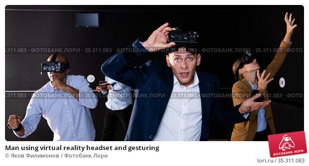 Man using virtual reality headset and gesturing. Стоковое фото, фотограф Яков Филимонов / Фотобанк Лори