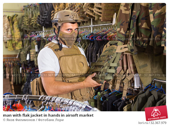 Купить «man with flak jacket in hands in airsoft market», фото № 32367979, снято 4 июля 2017 г. (c) Яков Филимонов / Фотобанк Лори