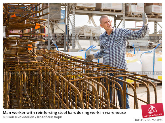 Man worker with reinforcing steel bars during work in warehouse. Стоковое фото, фотограф Яков Филимонов / Фотобанк Лори