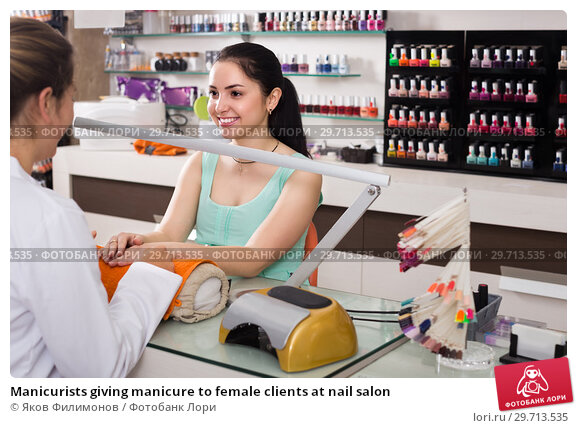 Купить «Manicurists giving manicure to female clients at nail salon», фото № 29713535, снято 28 апреля 2017 г. (c) Яков Филимонов / Фотобанк Лори