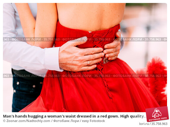 Man's hands hugging a woman's waist dressed in a red gown. High quality... Стоковое фото, фотограф Zoonar.com/Nadtochiy.com / easy Fotostock / Фотобанк Лори